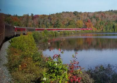 Canadian Train curves through autumn trees around a lake